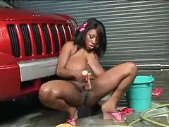 Curvy black chick gets wet washing the car tubes