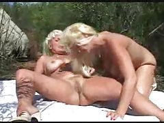 Two mature women make love in the grass tube
