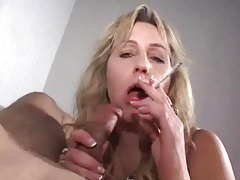 Lights a cigarette as she sucks dick tubes