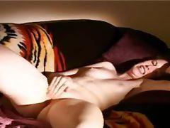Cute slender redhead masturbates on couch tubes
