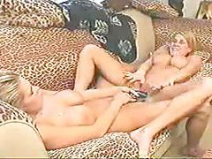 Two blondes share a big toy on the couch tubes