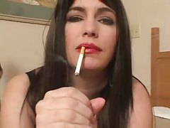 Busty chick in red lipstick smokes and strokes cock tubes
