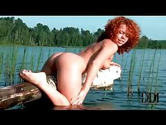 Curly haired redhead teases by the lake tubes