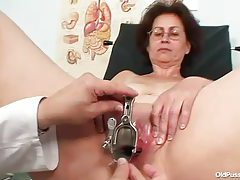 Mature in glasses takes speculum in pussy tubes