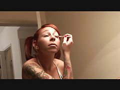 Heavily tattooed redhead with pigtails puts on makeup tubes
