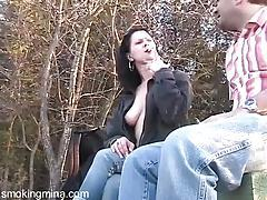 She blows him outdoors as they smoke tubes