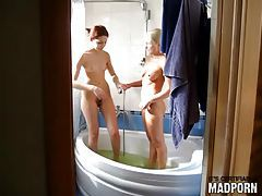 Cute teen girls laugh and soap up in bathtub tubes