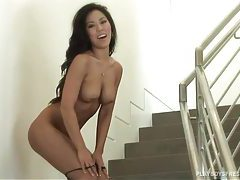 Asian stands on the stairs and teases her body tubes