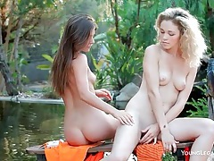Girls sit poolside and sensually fondle each other tubes