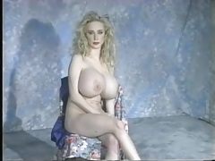 Solo blonde has gigantic fake tits to show off tubes