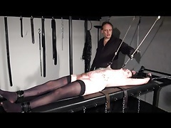 Girl on his table is bound and covered in hot wax tubes