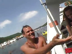 Topless girls model for guys on the boat tubes