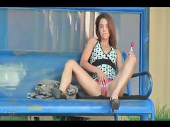 Hottie sucking a lollipop on a bus bench tubes