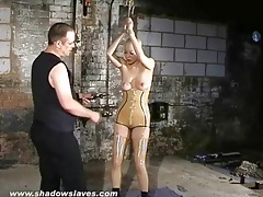 Girl in tight latex suffers through tit torture tubes