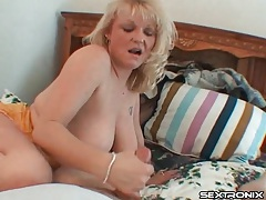 Mature blonde strokes his cock and sucks his balls tubes