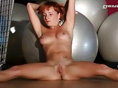 Redhead stretches naked in the gym tubes