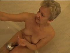 Shaved old pussy gets wet in the shower tubes