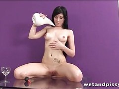 Brunette plays with a glass of piss tubes