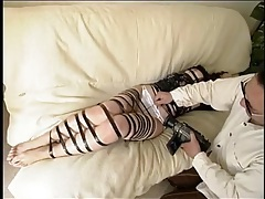 Girl bound by shiny black electric tape tubes