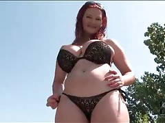Curvy redhead in sexy black bikini outdoors tubes