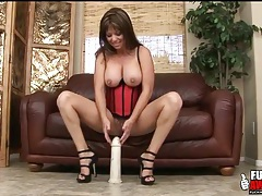 Milf in corset and heels sits on huge dildo tubes