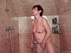 Mature gives a blowjob in the shower tubes