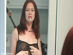 Redhead smokes in the mirror in black lingerie tubes