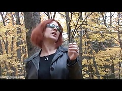 Redhead in leather jacket smokes in the woods tubes