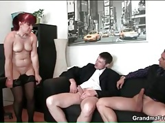 Mature redhead in oral threesome in the office tubes