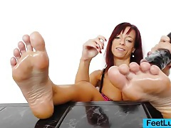 Redhead gives stirring footjobs to adult toy tubes