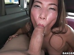 Asian brunette sucks off his cock in the car tubes