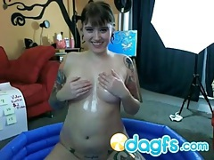 Tattooed webcam cutie totally covered in oil tubes