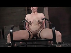 Sexy girl smiles as she sits in painful bondage tubes