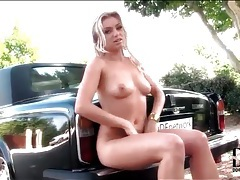 Naked blonde chick sits in an expensive car tubes