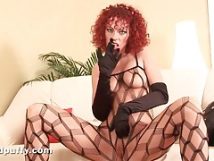Redhead in black lingerie plays with a toy tubes
