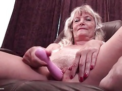 Granny sits on a desk and vibrates her clitoris tubes