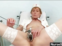 Slender mature nurse fucks cunt with a black toy tubes