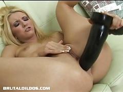 Raven haired slut sucks on a long dildo as it fucks her tubes