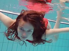 Teen in a pretty red dress slips into the pool tubes
