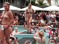 Topless babes in bikini bottoms dance at the pool tubes