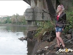 Blonde girl climbs down to the river to piss tubes