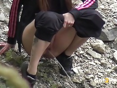 Sporty girl caught pissing down by the river tubes