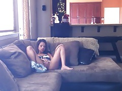 Spinner sits on the couch and fingers her hot cunt tubes