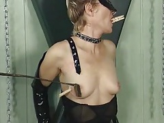 Clothes pins on the tits of a girl in black latex tubes