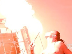 Topless big tits girl plays with fire tubes
