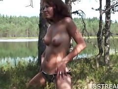 Amateur sweetheart in a swimsuit strips by the lake tubes
