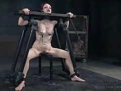 Tears run down the face of a redhead in bondage tubes