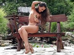 Naughty naked girl in the park fucks a dildo tubes
