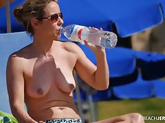 Milf at the beach rubs on sunscreen tubes