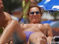Topless milf gets some sun in the sand tubes